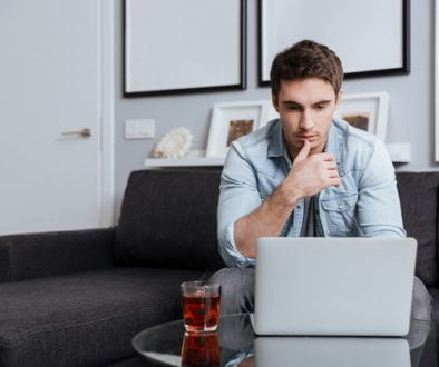 graphicstock-portrait-of-a-thoughtful-concentrated-man-looking-at-laptop-screen-while-sitting-on-sofa-at-home_HuMn_P283x